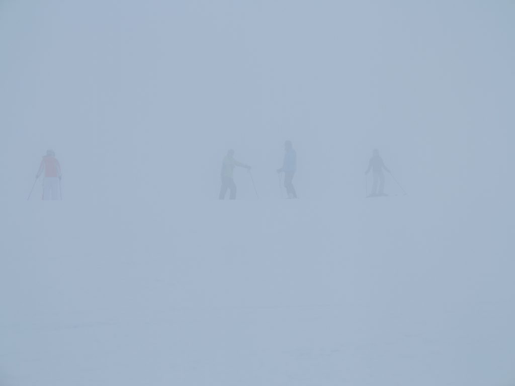 People Skiing On Snow Covered Field During Foggy Weather